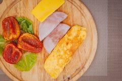 Омлет с ветчиной, зелеными цветами, сыром и подпертыми томатами служил на разделочной доске стоковая фотография