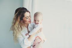 дом семьи счастливый Будьте матерью держать сына младенца в спальне в уютных выходных Стоковое фото RF