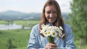 Она держит букет wildflowers и вытягивает их в камеру акции видеоматериалы