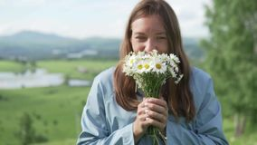 Она держит букет wildflowers и вытягивает их в камеру сток-видео