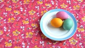 Она кладет дальше розовый поддонник скатерти с красочными пасхальными яйцами видеоматериал