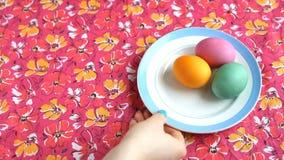 Она кладет дальше розовый поддонник скатерти с красочными яичками, тортом пасхи и ложкой сток-видео