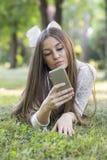 Она наслаждается outdoors и использованием мобильного телефона стоковые изображения