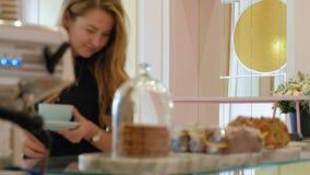 Она покупатель выбирает yummy Молодая привлекательная девушка, покупки женщины в кофейне или печенья, торты, торт, macaroon A видеоматериал