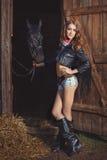 Она приносит лошадь от конюшен в вечере стоковые фотографии rf