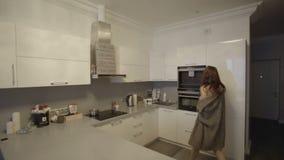 Она раскрывает холодильник в кухне видеоматериал