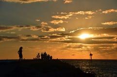 Она стоит самостоятельно на заходе солнца Стоковые Фотографии RF