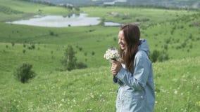 Она стоит с букетом цветков в поле и вдыхает их нюх сток-видео