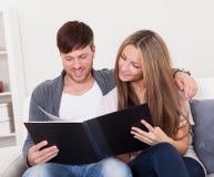 Они смотрят альбом семейного фото Стоковое Изображение RF