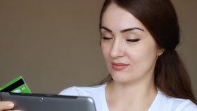 Онлайн-банкинги молодой женщины используя планшет, ходить по магазинам онлайн на магазине интернета и приобретение через кредитны акции видеоматериалы