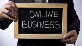 Онлайн дело написанное на классн классном, бизнесмене держа знак, независимый Стоковое Изображение