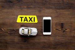 Онлайн заказ комплект такси с игрушкой автомобиля и чернь на деревянной насмешке взгляд сверху предпосылки вверх Стоковое Изображение RF