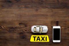 Онлайн заказ такси с передвижным модель-макетом взгляд сверху предпосылки деревянного стола app и автомобиля модельным Стоковая Фотография RF