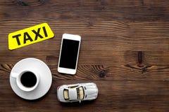 Онлайн заказ такси с передвижным модель-макетом взгляд сверху предпосылки деревянного стола app и автомобиля модельным Стоковое фото RF