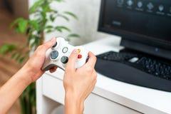 Онлайн-игра счастливого молодого человека играя и выигрывая на компьютере Задний взгляд gamer с видео- регулятором gamepad консол стоковое изображение