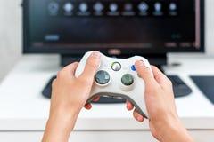 Онлайн-игра счастливого молодого человека играя и выигрывая на компьютере Задний взгляд gamer с видео- регулятором gamepad консол стоковые изображения