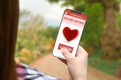 Онлайн идея датировка, девушка с frameless телефоном на запачканной предпосылке природы стоковые фотографии rf