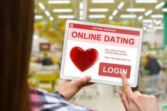 Онлайн концепция датировка, девушка держит цифровую таблетку на запачканной предпосылке магазина стоковое фото