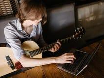 Онлайн курсы музыки учат гитару игры стоковые фото