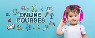 Онлайн курсы с мальчиком малыша с наушниками стоковые фото