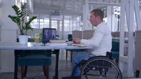 Онлайн обучение, студент неработающий в кресло-коляске делая примечания в тетради во время далекого образования сидя на таблице с акции видеоматериалы