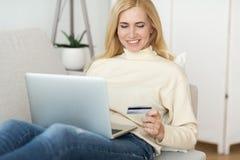 Онлайн-платеж Приобретение женщины одевает онлайн на ноутбуке стоковые изображения