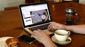 Онлайн покупки вахты на вебсайте ` s eBay на экране портативного компьютера MacBook Pro видеоматериал