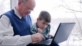 Онлайн приобретение, дед с внуком высчитано электронными деньгами на интернете через компьютер в комнате сток-видео