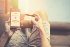 Онлайн ходя по магазинам человек используя покупки смартфона в рынке вебсайта онлайн и руки держа кредитную карточку стоковое изображение