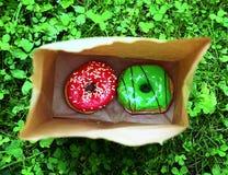 2 донута с поливой мяты и клубники в бумажной сумке на зеленом конце предпосылки лужайки вверх Стоковое Изображение RF