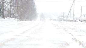 Он автомобиль едет вдоль снежной дороги, зимы и сильной вьюги видеоматериал