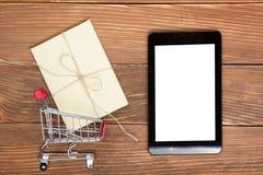 Онлайн концепция покупок - пустые магазинная тележкаа, компьтер-книжка и ПК таблетки, подарочная коробка на деревенской деревянно стоковая фотография rf