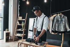 Он имеет большой стиль Серьезный молодой человек аранжируя мужская одежда пока стоковая фотография rf