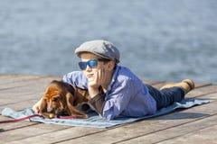 Он наслаждается с его собакой морем стоковые фото