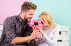 Он угадал ее любимый цветок цветет она Человек дает цветки букета к подруге Женщина человека сидит стенд романтичный Стоковое фото RF