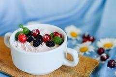Опарникы естественного белого йогурта с фруктовым салатом с розовыми плодом, ягодами и мятой дракона на деревянной таблице Здоров стоковое фото rf