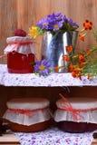 Опарникы различных варениь и металлического кувшина с цветками стоковое изображение rf