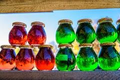 Опарникы с красным и зеленым медом для продажи как сувенир в рынке outdoors стоковые изображения