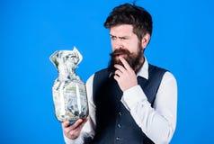 Опарник владением хипстера человека бородатый вполне наличных денег Держать вопросы наличных денег Бизнесмен с его сбережениями д стоковые фотографии rf
