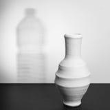 Опарник гончарни выпивая с тенью пластичной бутылки с водой Стоковые Изображения RF