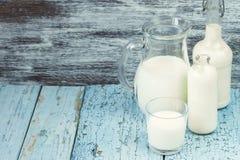 Опарник и бутылки с молоком, и полное стекло с молоком Стоковое Фото