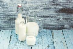 Опарник и бутылки с молоком, и полное стекло с молоком Стоковые Изображения