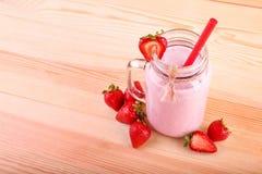Опарник каменщика с ручкой, красной соломой и красивым розовым milkshake на деревянной предпосылке Стекло сладостного коктеиля кл Стоковая Фотография RF