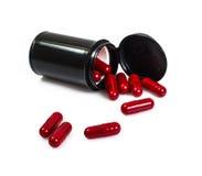 Опарник красной капсулы медицинский в черноте на белой предпосылке Стоковые Изображения