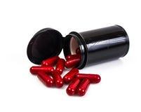 Опарник красной капсулы медицинский в черноте на белой предпосылке Стоковое Изображение