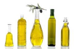 Опарник различного оливкового масла стеклянный, с ветвью листьев и черных ягод na górze одного на белом backgound Стоковая Фотография