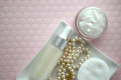 Опарник роскошных сливк стороны красоты и бутылки сыворотки с жемчугами на розовой предпосылке цвета с космосом экземпляра Стоковое Изображение