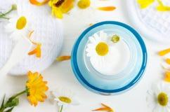 Опарник синего стекла Ligh с белыми лицевыми сливк/маской ¡ Ð hamomile и calendula цветут на белой предпосылке Стоковые Изображения RF