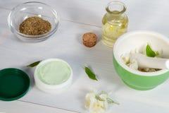 Опарник сливк сделанный из естественных ингредиентов завода, масел и трав, цветков жасмина, миномета и пестика на белое деревянно стоковая фотография