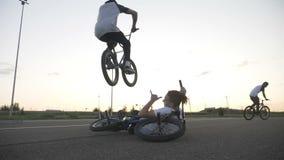 Опасная скачка выполнила опытным холодным велосипедистом над его расслабленным другом сидя вниз с его велосипедом в замедленном д акции видеоматериалы